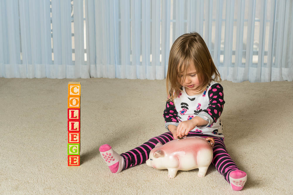 young girl on the floor with a piggy bank and blocks arranged to spell college